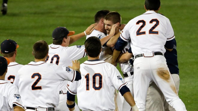 Virginia players swarm first baseman Mike Papi, center, after he hit a double in the ninth inning against Missisippi that scored Thomas Woodruff to win their College World Series opener Sunday in Omaha, Neb.