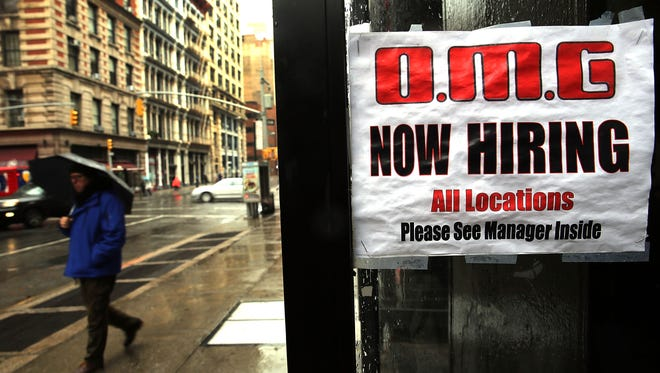 A sign in a window at a retail store advertises for a job opening in New York City in December.