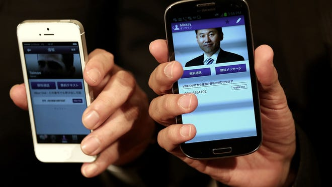 Hiroshi Mikitani, chairman and chief executive officer of Rakuten, is pictured in the Viber app on the phone of Talmon Marco, chief executive officer of Viber.