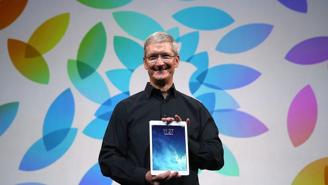 Apple CEO Tim Cook holds the new iPad Air.
