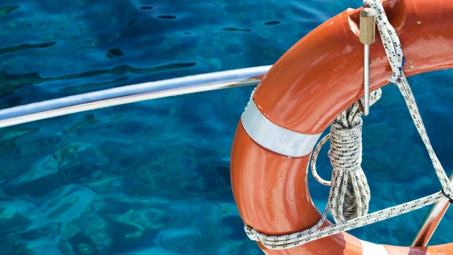 A life preserver tied to boat in the open water.