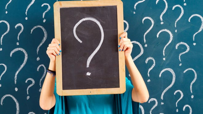 Woman holding chalkboard with question mark.