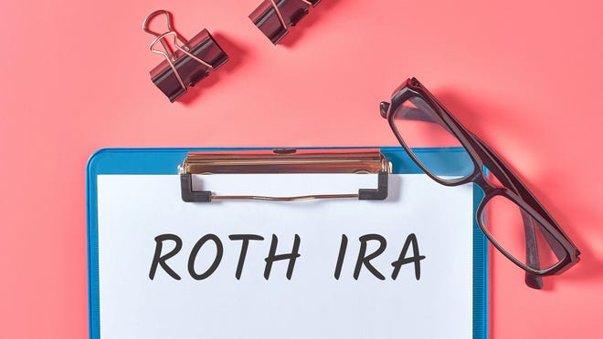 Roth IRA on clipboard with glasses.