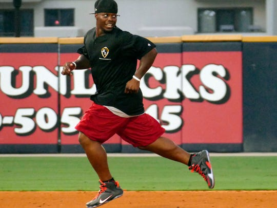 Football player Trent Richardson races to third base