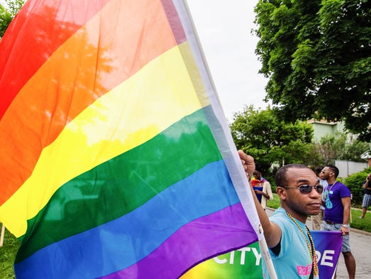 Luke Sinnette of Trinidad and Tobago stands at attention waiting for the parade to begin as part of the Iowa City Pride Parade prior to making its way through downtown Iowa City on Saturday, June 21, 2014.