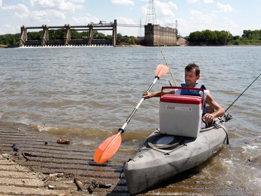 Bobby Kitchen, of Louisville, launches his kayak into the Ohio River from the George Rogers Clark Homesite boat ramp in Clarksville, Ind. The McAlpine hydroelectric dam is in the background.  July 9, 2014