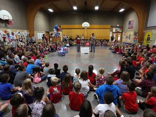 Students surround kindergarten teacher Brittney Lau and Bill Haack during the ceremony at Woodside Elementary School in Wisconsin Rapids on Monday, Sept.  21, 2015, at which Haack received more than $900, hand-painted dishes and kitchen supplies for his American Heroes Cafe Central Wisconsin.