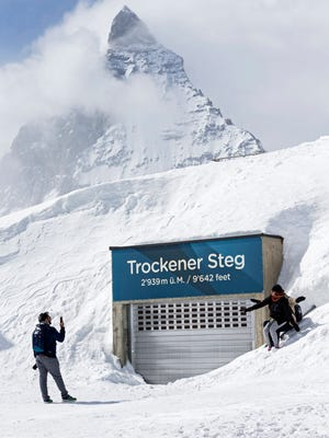 Indian tourists take a photograph in front of a garage and the Matterhorn mountain, at the gondola station 'Trockener Steg' where the last mobile phone signal of the missing German businessman Karl-Erivan Haub, CEO of the German Tengelmann Group, was detected, in Zermatt, Switzerland, April 12, 2018.