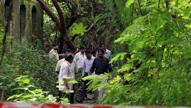 Indian policemen inspect the site where a 22-year-old woman was gang raped in Mahalaxmi area in Mumbai, India, Friday,