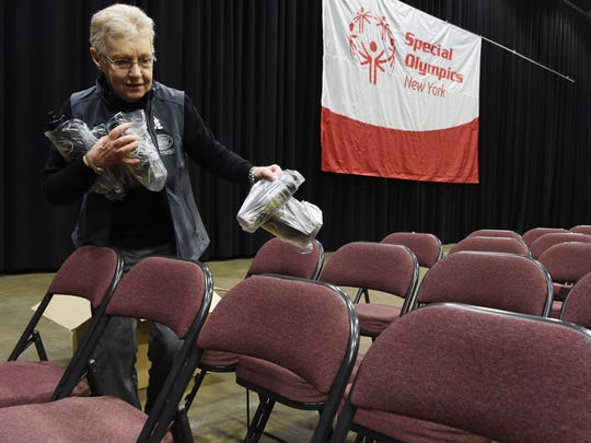 Linda Rodrian, marketing assistant at the Poughkeepsie Galleria, sets up water bottles underneath chairs for the opening ceremony of the Special Olympics New York Winter Games at the Mid-Hudson Civic Center in the City of Poughkeepsie.