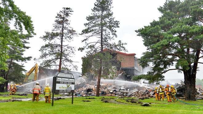 A backhoe takes down sections of the building as firefighters from St. Cloud and several other departments continued to fight a fire that destroyed the Roosevelt Education Center.