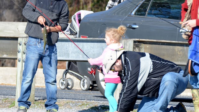 A young man helps a little girl with her trout during the Mentored Youth Trout Fishing Day last weekend.