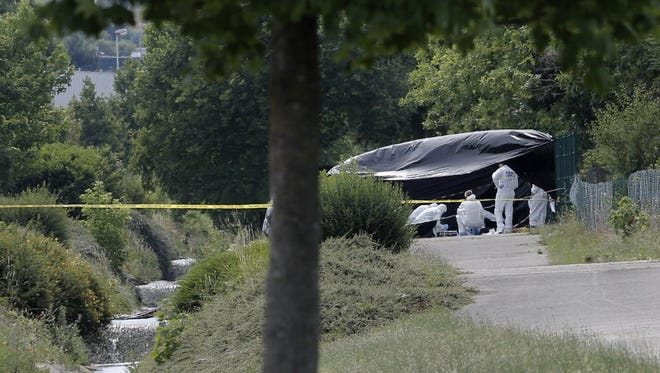 Police officers investigate near a factory where an attack took place on June 26, southeast of Lyon, France.
