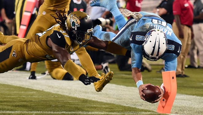Marcus Mariota of the Titans dives for a touchdown in front of Johnathan Cyprien of the Jaguars during the third quarter.