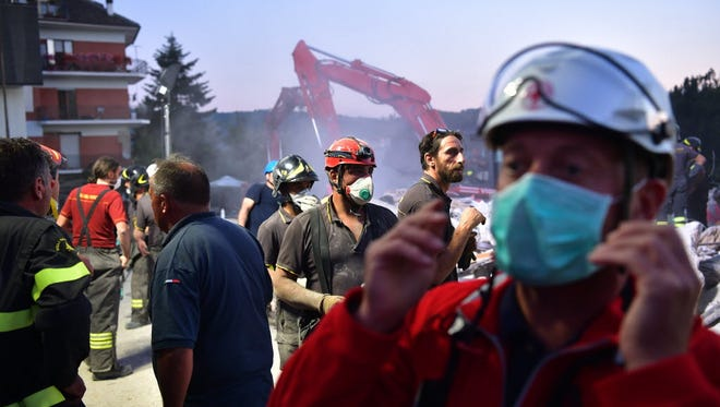 Emergency workers search the rubble of a building that was destroyed during an earthquake Aug. 25, 2016, in Amatrice, Italy.