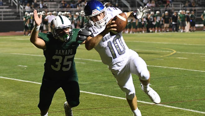 Austin Albericci (10) passed for three touchdowns and ran for two more to lead NV/Demarest over Dwight Morrow.