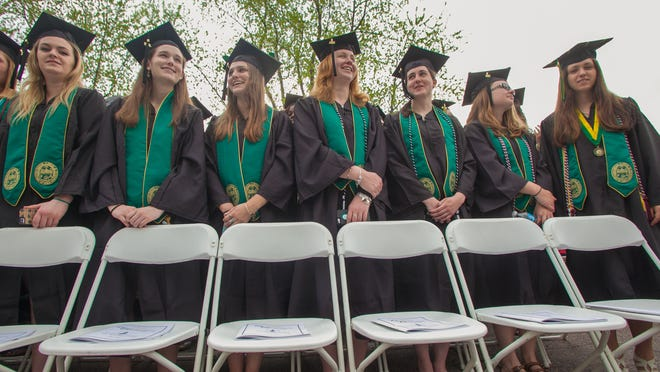 From left, Zoe Hraska, Hollary Turner, Chelsea Radley, Victoria Gerald, Samantha Cox, Madeleine Hassett, and Sam D'amico, graduating University of Vermont students, stand near the front row of the commencement ceremony Sunday