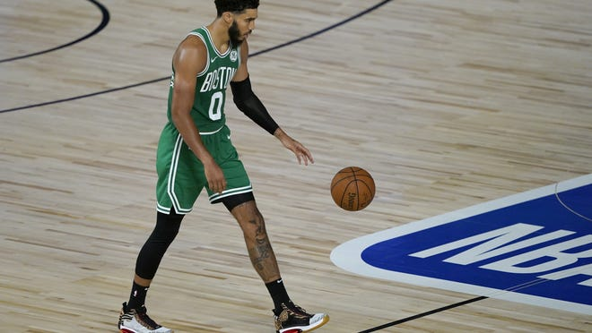 Boston Celtics' Jayson Tatum brings the ball down the court during the second half of an NBA basketball game against the Milwaukee Bucks on Friday in Lake Buena Vista, Fla.