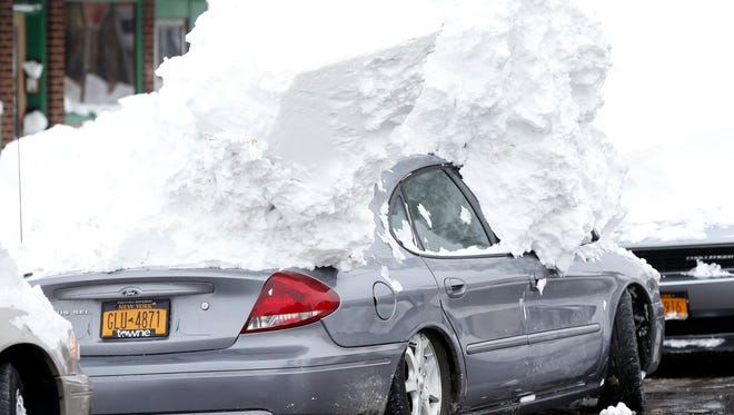 A car is weighed down by heavy snow in the south Buffalo on Saturday.