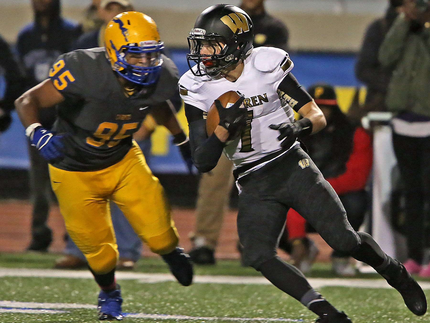 Warren Central quarterback Zach Summeier #7 keeps the ball as Carmel's #95 Rodney Haywood closes in during the Warren Central at Carmel High School football game, Friday, October 9, 2015. Carmel won 30-20.