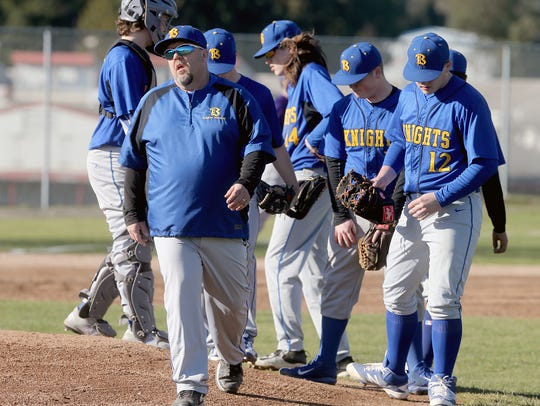 Bremerton baseball coach Steve Dickey finishes a conversation with his players during a game against North Kitsap.