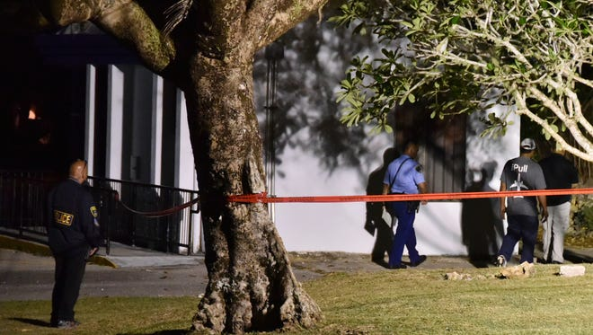 Guam Police Department officers tape sections off an area of a park in Talofofo next to San Miguel Catholic Church late Saturday night. v