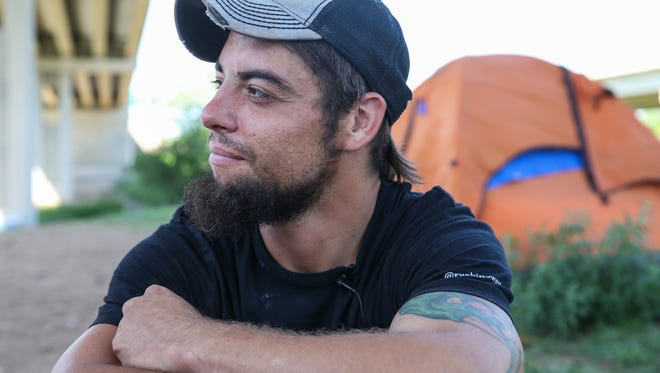 Dustin Halvorson hangs out in tent city under the Houston Harte Expressway in San Angelo.