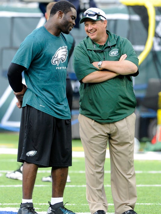 FILE - In this Aug. 29, 2013, file photo, then-Philadelphia Eagles quarterback Michael Vick, left, talks to New York Jets offensive coordinator Marty Mornhinweg before a preseason NFL football gamein East Rutherford, N.J. It might seem a little like old times for Michael Vick and Marty Mornhinweg on Sunday. Just a few years ago, Vick revived his career in Philadelphia with Mornhinweg as his offensive coordinator. With Geno Smith benched, Vick is getting a chance to start again _ and spark Mornhinweg's struggling offense with the New York Jets. (AP Photo/Bill Kostroun, File)