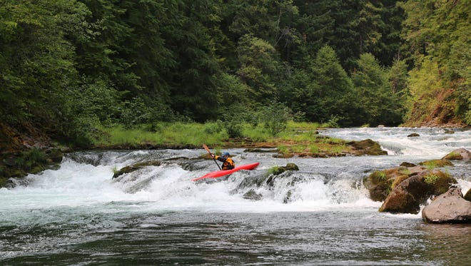 "A kayaker paddles through ""Right or Left"" rapid on the North Fork of the Rogue River, downstream of River Bridge Campground."
