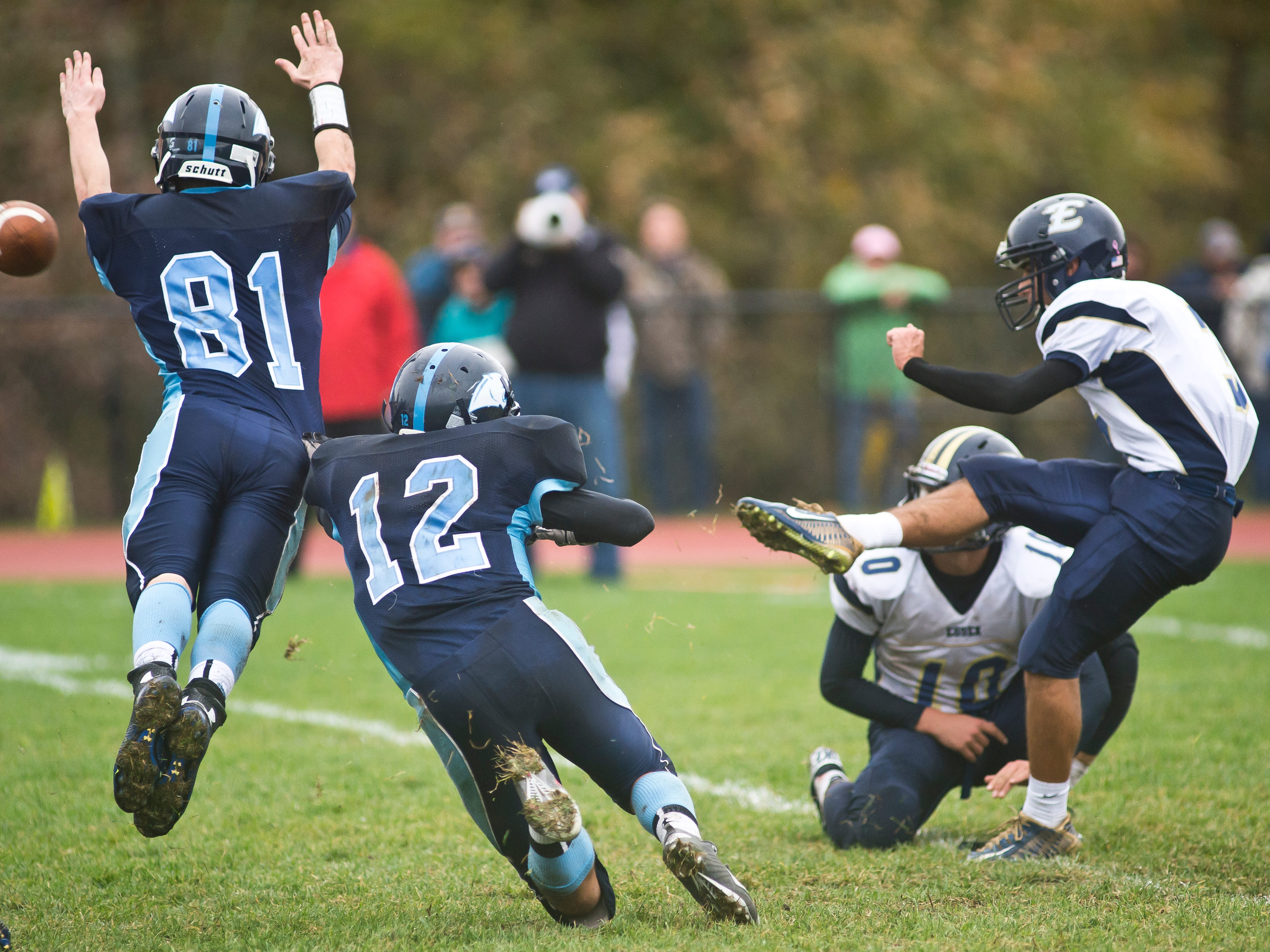 MMU's #81Justin Fischer and #12 Dominic Mosca manage to put the pressure on Essex #3 Matthew Olsen, forcing an extra point attempt wide during Saturday's game in Jericho.