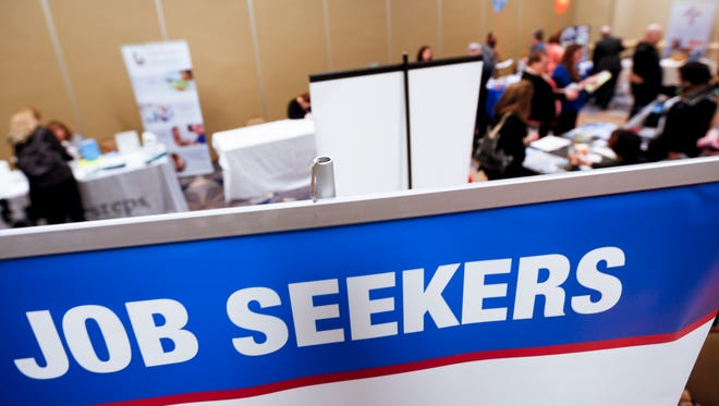 In this photo made on Wednesday, March 30, 2016, display signs designed to attract employment seekers line the booths of job recruiters at a Job Fair.
