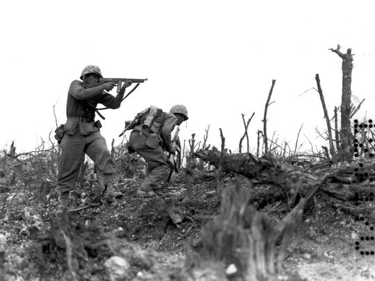 A U.S. Marine of the 1st Division takes aim and fires with his machine gun at a Japanese sniper as his comrade ducks for cover.