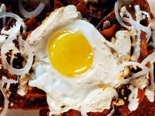 Chilaquiles from Joy Bus Diner include crisp chile drenched tortilla chips with an egg, queso fresco and crema drizzled on top for garnish.