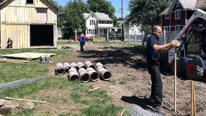Contractor Ken Miller pounds a stake on the site of a new building that will replicate a barracks from the Elmira Civil War Prison Camp. In the background is the only surviving building from the camp, which was recently reassembled at a site on Winsor Avenue in Elmira.