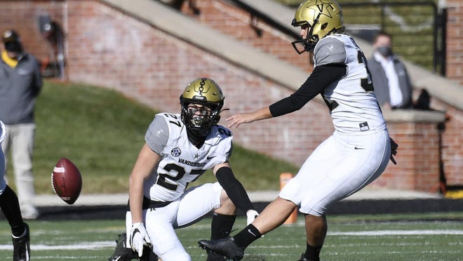 Vanderbilt's Sarah Fuller, right, kicks off as Ryan McCord (27) holds to start the second half of an NCAA college football game against Missouri on Saturday in Columbia, Mo. With the kick, Fuller became the first female to play in a Southeastern Conference football game.