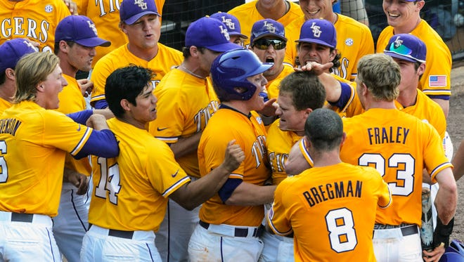 LSU celebrates with Sean McMullen after his two-run blast gave the Tigers a 2-0 lead in the eighth inning during their NCAA college baseball SEC tournament championship game against Florida, Sunday, May 25, 2014, at the Hoover Met in Hoover, Ala.