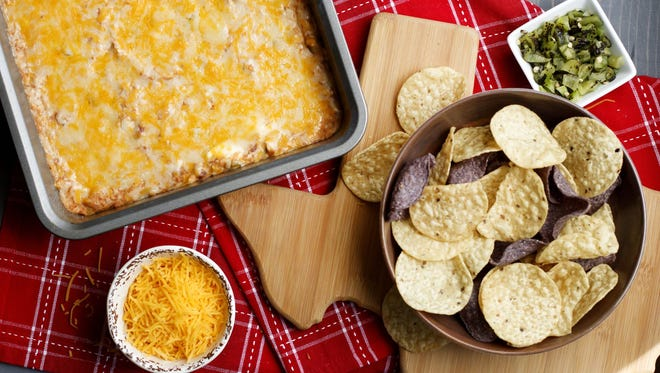 Texas Trash Dip combines cream cheese, green chiles, Mexican cheese blend, refried beans, sour cream and McCormick® Taco Seasoning Mix.