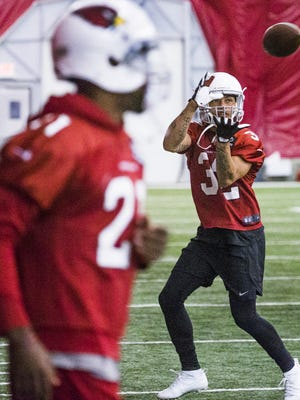 Arizona Cardinals safety Tyrann Mathieu, right, catches a ball as cornerback Patrick Peterson, left, runs back to formation during practice in the bubble at the Tempe facility, Thursday, June 8, 2017.