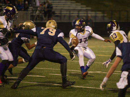 Waynesboro quarterback Chris Baker makes a quick change of direction to avoid Hidden Valley defenders before throwing a touchdown to take the lead 12-0 during their group 3A first round playoff game in Roanoke on Friday, Nov. 14, 2014.