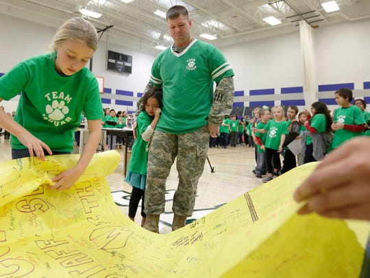 Kindergartener Bianca Withers leans into her father, U.S. Army Staff Sgt. Joshua Withers, while students roll up a welcome banner Friday morning at Thomas Jefferson Elementary School.