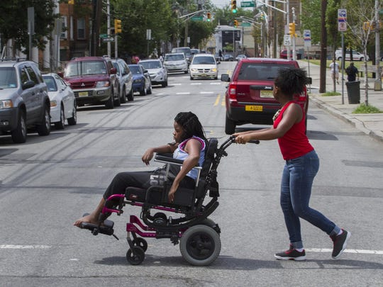 Brielle Johnson pushes her cousin Yesenia Parker as they return home from Audubon Park.