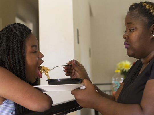 Shandar Parker feeds lunch to her daughter Yesenia in their Jersey City apartment.