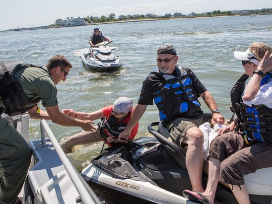 Corporal Brad Bunting helps Peggy Bender, of Lebanon, Pennsylvania, onto his patrol boat after she fell off a jet ski.