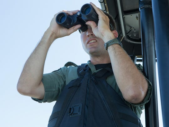 Officer Robert Duvall, scans the bay near West Ocean City for boat safety violations on Friday.