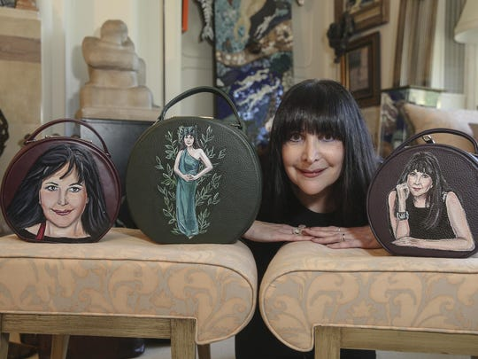 In this Thursday, Sept. 19, 2019 photo, Ilene Wood poses with handbags featuring paintings of her at her Lehigh Valley Estate in Emmaus, Pa. Ilene Hochberg Wood's collection of 3,000 handbags — the majority of which dwell in a 2,400-square-foot Quonset hut on her Lehigh Valley estate — will make a fashionista fall to her knees. ( Steve M. Falk/The Philadelphia Inquirer via AP)
