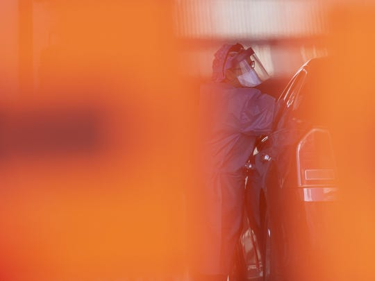 A health care professional administers a coronavirus test at a drive-thru site in Camden, N.J., Wednesday, April 1, 2020. (Joe Lamberti/Camden Courier-Post via AP)