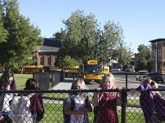 Fourth grade students attending Park Elementary School line up across the road at the bus depot while waiting their turn to enter the school on the first day back in Casper, Wyo., on Sept. 2.
