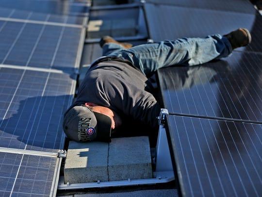 TJ Swan, with Rectify Solar, reaches underneath a solar