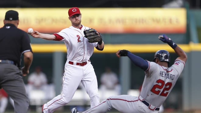 Cincinnati Reds shortstop Zack Cozart (2) turns a double play. Manager Bryan Price said Cozart will be the Reds' starting shortstop in 2015 during Spring Training.