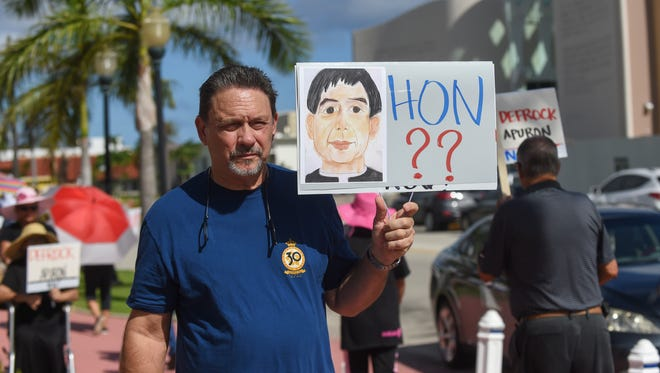 Bruce Williams protests with a sign that displays an illustration of Archbishop Savio Tai Fai Hon at the Dulce Nombre de Maria Cathedral Basilica in Hagatna on July 17.